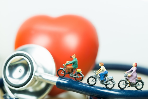 Small figures riding on stethoscope and red heart with white backgrounds.