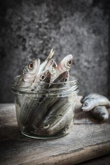 Small fish plated in a dark mood scene.