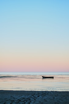 Small fishing boat in bay at dusk sunset