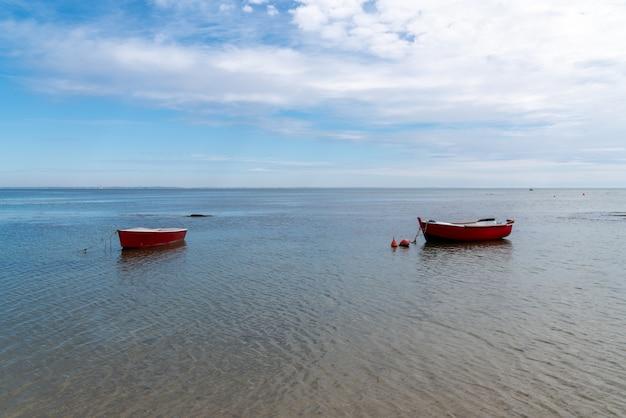 Small fishing boat on calm sea low tide in noirmoutier