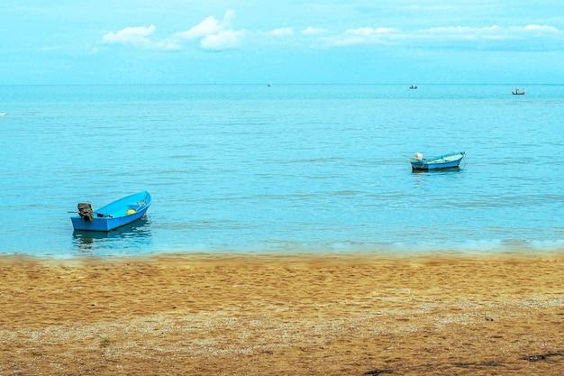 Маленькая рыбацкая лодка, плавающая в синем море с голубым небом, таиланд рыбацкая лодка или рыбацкая лодка или корабль на sam roi yod bech prachuap khiri khan таиланд с голубым небом и облаками и синим морем.