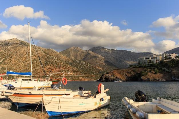크레타, rethymno, 그리스에서 배경에서 산들과 작은 낚시 보트.