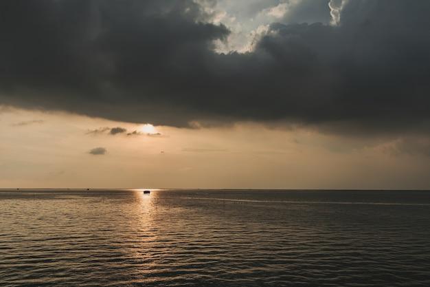 日没と海の真ん中にある小さな釣り小屋