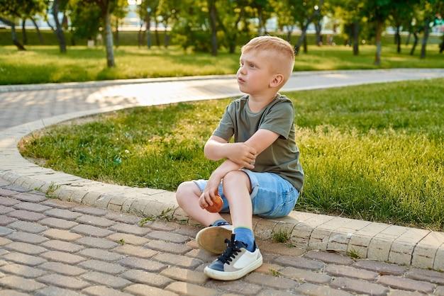 小さな5歳の赤毛の少年は、腕に絆創膏でひじを打撲し、動揺しています