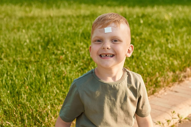 小さな5歳の赤毛の少年は、頭にパッチを当てて公園の芝生に座っている額を傷つけました