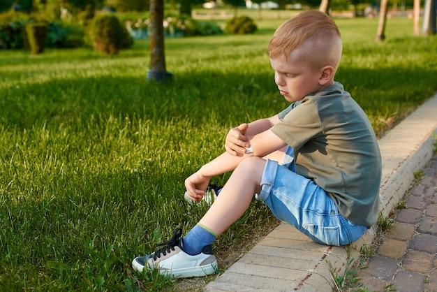 小さな5歳の赤毛の少年が公園の道路に座って、ひじに傷を接着しています