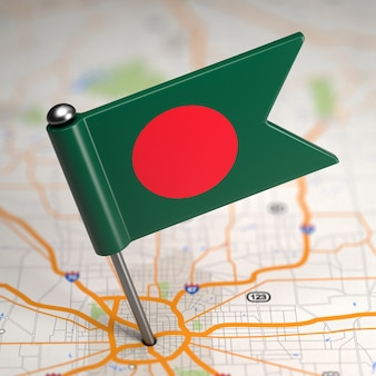 Small flag of bangladesh on a map background with selective focus.