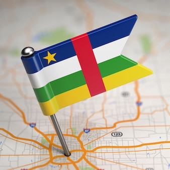 Small flag of central african republic on a map background with selective focus.