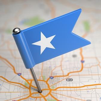 選択的な焦点と地図の背景にソマリア連邦共和国の小さな旗。