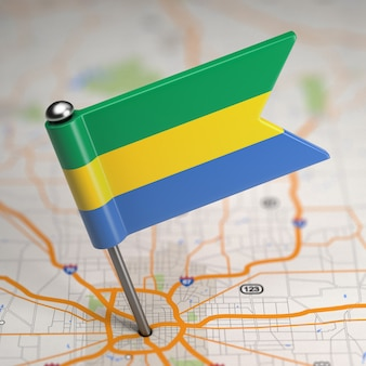 Small flag gabonese republic on a map background with selective focus.