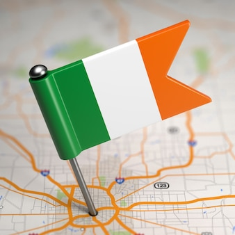 Small flag of ireland sticked in the map background with selective focus.