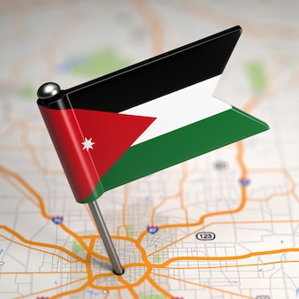 Small flag of jordan on a map background with selective focus.