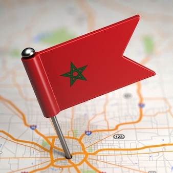 Small flag of morocco on a map background with selective focus.
