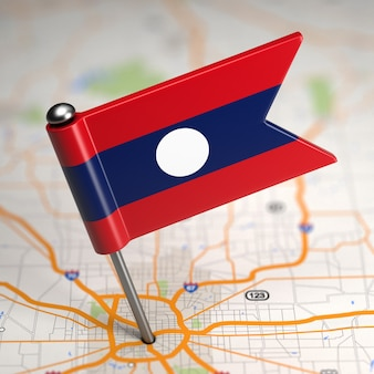 Маленький флаг лаосской народно-демократической республики на фоне карты с выборочным фокусом.