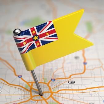 選択的な焦点と地図の背景にニウエの小さな旗。