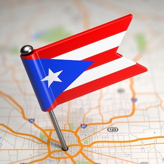 Small flag of puerto rico on a map background with selective focus.