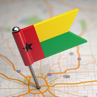 Small flag republic of guinea-bissau on a map background with selective focus.