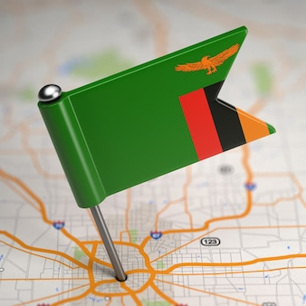 Small flag republic of zambia on a map background with selective focus.
