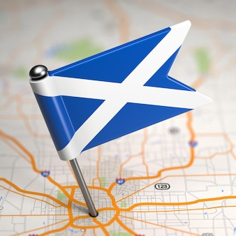 Small flag of scotland on a map background with selective focus.