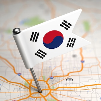 Small flag of south korea on a map background with selective focus.