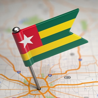 Small flag togolese republic on a map background with selective focus.