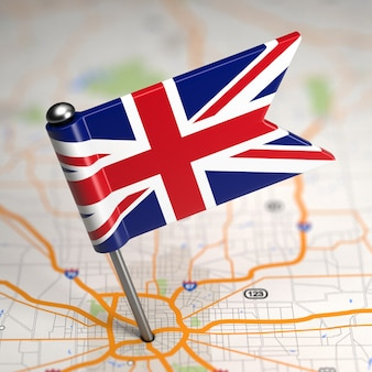 Small flag of united kingdom of great britain on a map background with selective focus.