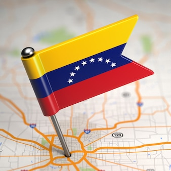 Small flag of venezuela on a map background with selective focus.