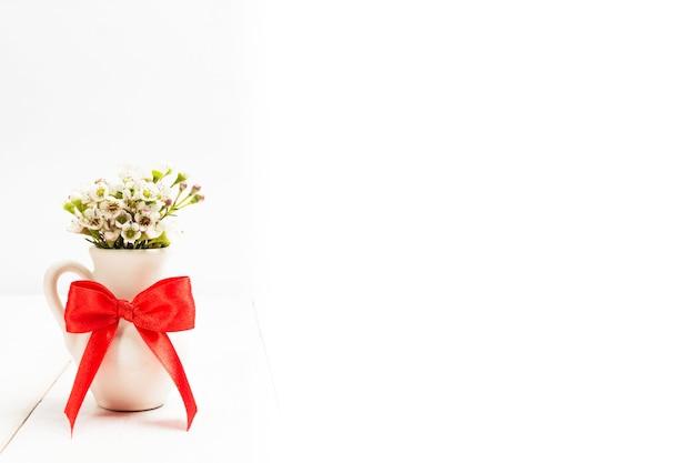 붉은 활과 꽃병에 작은 꽃