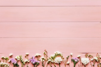 Small flowers on pink wooden table