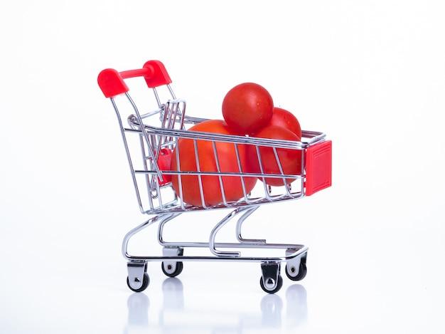 Маленькая продуктовая корзина на колесах с красными помидорами черри на белом