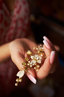 Small in the form of flowers golden hairpin in the hand of a girl