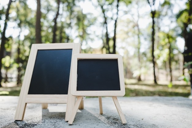 Small a-frame blackboard with blank area for text or message on rustic wood table in morning time