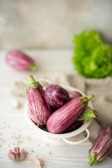 Small fresh striped eggplant with greens on a white table