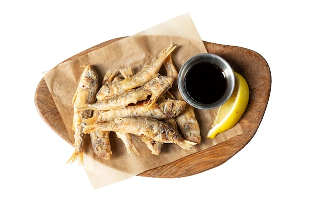 Small fried fish with lemon and sauce on a wooden board