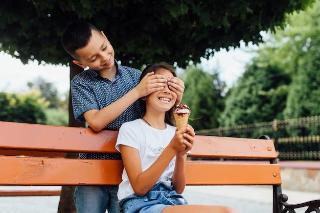 アイスクリームボーイを食べているベンチの小さな友達は彼の妹の目を閉じた