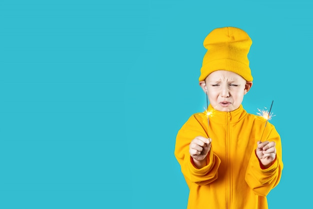 A small frightened child in yellow hat and jacket holds burning sparklers in his hands on a blue background