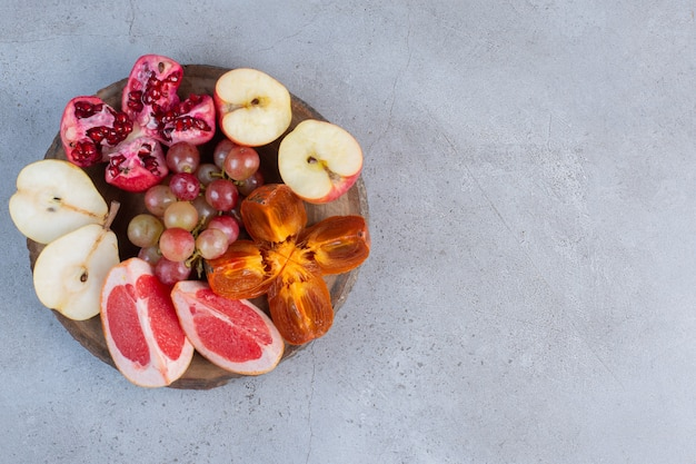 A small fruit assortment on a wooden board on marble background.