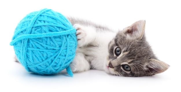 Маленький забавный котенок и клубок ниток. изолированные на белом фоне