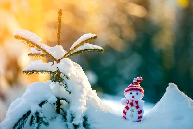 밝은 파란색과 흰색 복사 공간 배경에서 야외 깊은 눈에 니트 모자와 스카프에 작은 재미있는 장난감 아기 눈사람. 새 해 복 많이 받으세요 그리고 기쁜 성 탄 인사말 카드입니다.