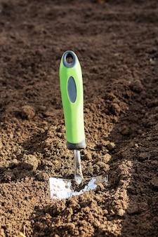 Маленькая садовая лопата застряла в земле крупным планом