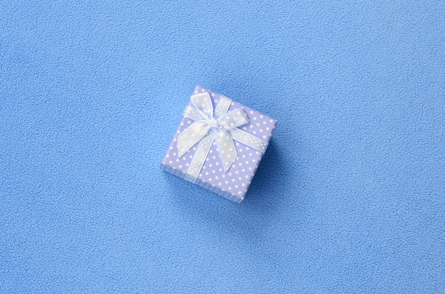 A small gift box in blue with a small bow lies on a blanket of soft and furry light blue fleece fabric.