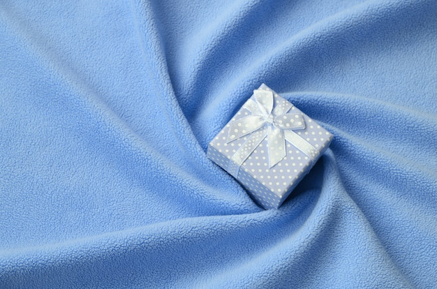 A small gift box in blue with a small bow lies on a blanket of soft