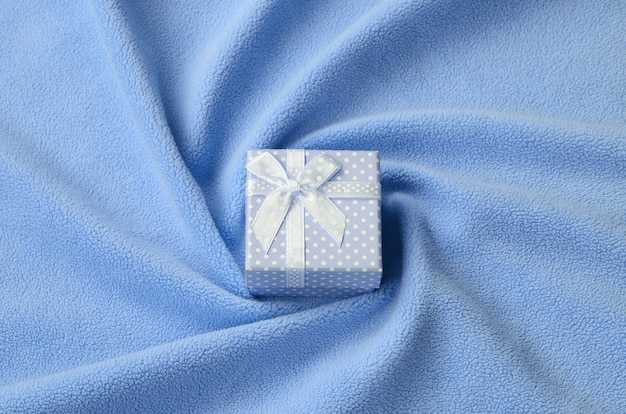A small gift box in blue with a small bow lies on a blanket