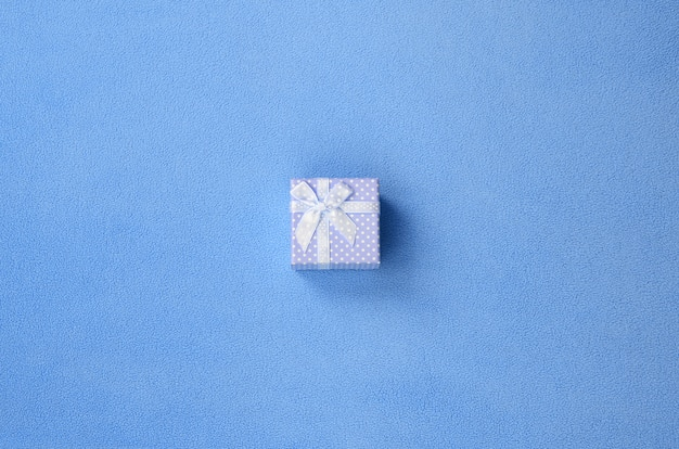 A small gift box in blue with a small bow