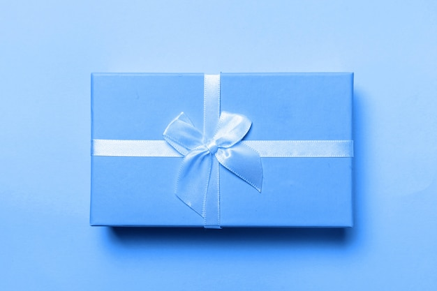 Small gift box colored in trendy color of year 2020 classic blue background. bright macro color . christmas new year birthday valentine celebration present romantic .