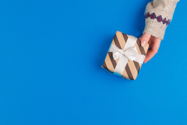 Small gift box in female hands on blue background, view from above