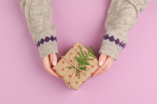 Small gift box in female hands, view from above