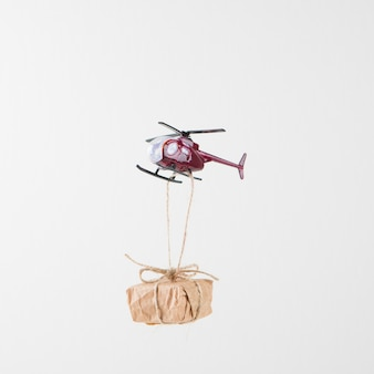 Small gift box hanging on flying helicopter