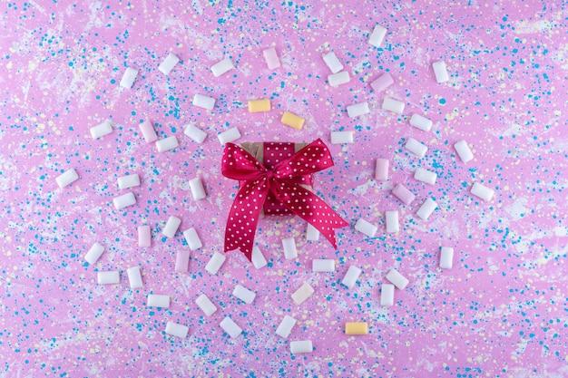 Piccola confezione regalo al centro di un fascio di gomme da masticare sparse su una superficie colorata