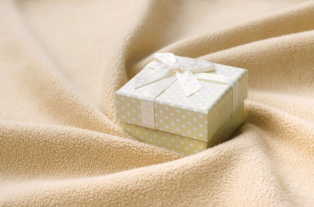 A small gift box in orange with a small bow lies on a blanket